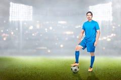 Fachowa azjatykcia gracz piłki nożnej mężczyzny pozycja z piłką na jego nodze zdjęcia stock