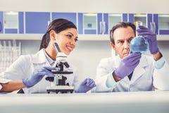 Fachowa biolożka pokazuje szklanej tubki jego asystent obraz stock