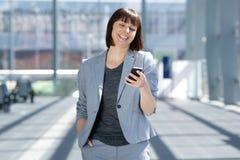 Fachowa biznesowa kobieta ono uśmiecha się z telefonem komórkowym Zdjęcia Royalty Free