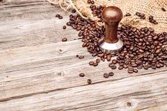 Fachowa drewniana kawowa stemplówka z kawowymi fasolami i workiem na drewnianym tle, produkt fotografia dla sklep z kawą obraz royalty free