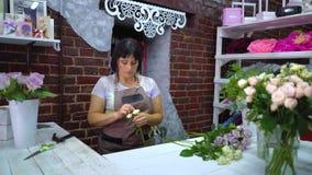 Fachowa kwiaciarnia rozjaśnia biel róży gałąź od suchych płatków i sprawdza zbiory wideo