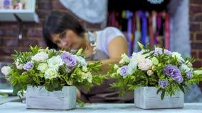 Fachowa kwiaciarnia układa pięknego kwiatu skład w drewnianym pudełku w kwiecistego projekta studiu Zdjęcie Royalty Free