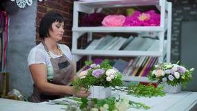 Fachowa kwiaciarnia układa pięknego kwiatu skład w drewnianym pudełku w kwiecistego projekta studiu zbiory wideo