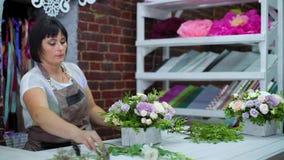 Fachowa kwiaciarnia układa pięknego kwiatu skład w drewnianym pudełku w kwiecistego projekta studiu zbiory