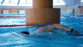 Fachowa męska pływaczka ćwiczy w pływackim basenie Młody sportowa dopłynięcie w basenie swobodny ruch zdjęcia royalty free