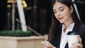 Fachowa młoda bizneswoman pozycja na miastowej ulicznej używa smartphone i napoju kawie Pojęcie: nowy biznes zbiory