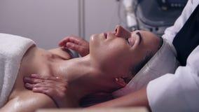 Fachowa młodości opieka w zdroju salonie Młoda kobieta jest odbiorczym szyi i twarzy masażem robić fachowym cosmetologist zbiory