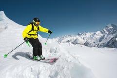 Fachowa narciarka przy prędkością przed skakać od lodowa w zimie przeciw górom i niebieskiemu niebu fotografia stock