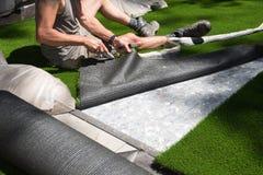 Fachowa ogrodniczka jest tnącym sztucznym murawą dostosowywać fotografia royalty free