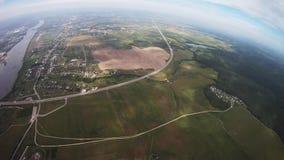 Fachowa spadochronowa bluza lata above zieleni pole, rzeka Popielaty chmurny niebo zbiory wideo