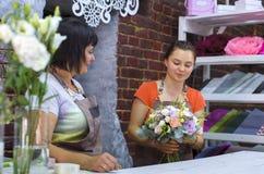 Fachowe kwiaciarnie układa kwiatu ślubnego bukiet w kwiecistego projekta studiu obraz stock