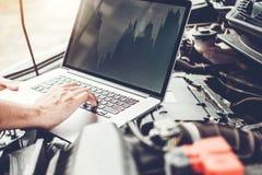 Fachowe technik ręki sprawdzać samochodowego silnika remontowej usługi używać laptop na samochodzie obraz royalty free