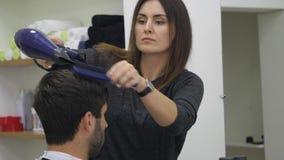 Fachowego fryzjera suszarniczy włosy w piękno salonie Męski młodego klienta i kobiety fryzjer męski z bliska zbiory wideo