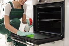 Fachowego janitor czyści piekarnik z gąbką w kuchni zdjęcie stock