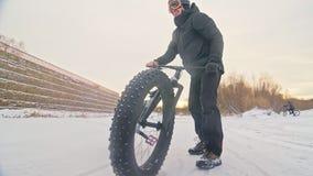 Fachowego krańcowego sportowa rowerzysty jeździecki gruby rower w plenerowym Cyklista przejażdżka w zima śnieżnym lasowym mężczyź zbiory