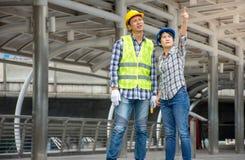 Fachowej Azjatyckiej inżynierii drużynowy jest ubranym zbawczy hełm opowiada o projekcie budowlanym i wskazuje palec up przy zdjęcia stock