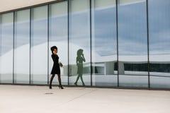 Fachowej kobiety odprowadzenie i opowiadać na telefonie komórkowym outside obraz royalty free