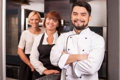 Fachowi życzliwi szefowie kuchni pracują w piekarni obrazy stock