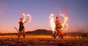 Fachowi artyści pokazują pożarniczego przedstawienie przy lato festiwalem na piasku w zwolnionym tempie Fourth osoba akrobaci od zdjęcie wideo