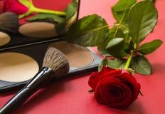 Fachowi kosmetyki koryguje proszek, muśnięcie i wzrastali na czerwień textured powierzchni Obraz Stock