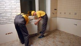 Fachowi pracownicy instaluje ogrzewa? w nowym domu fotografia royalty free