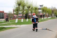 Fachowi strażacy, ratownicy w ochronnym fireproof kostiumy, hełmy i maski gazowe z tlenowymi butelkami przygotowywają rescu Fotografia Stock