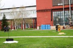 Fachowi strażacy, ratownicy w ochronnym fireproof kostiumy, hełmy i maski gazowe z tlenowymi butelkami przygotowywają rescu Zdjęcia Royalty Free