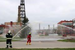 Fachowi strażacy w pomarańczowych fireresistant kostiumach w białych hełmach z maskami gazowymi badają pożarniczych węże elastycz fotografia royalty free
