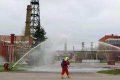 Fachowi strażacy w pomarańczowych fireresistant kostiumach w białych hełmach z maskami gazowymi badają pożarniczych węże elastycz zdjęcie stock