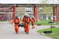 Fachowi strażaków ratownicy w pomarańczowych ochronnych fireresistant kostiumach, białych hełmach i maskach gazowych, znoszą zdra obrazy stock