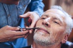 Fachowy ładny fryzjer męski przygotowywa jego klient brodę Fotografia Stock