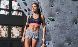 Fachowy żeński arywista opiera na bouldering ścianie przy gym fotografia stock