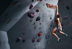 Fachowy żeński arywisty obwieszenie na bouldering ścianie, praktyka wspina się indoors obrazy stock