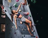 Fachowy żeński arywisty obwieszenie na bouldering ścianie, praktyka wspina się indoors obrazy royalty free