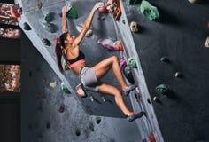 Fachowy żeński arywisty obwieszenie na bouldering ścianie, praktyka wspina się indoors zdjęcie royalty free