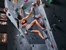 Fachowy żeński arywisty obwieszenie na bouldering ścianie, praktyka wspina się indoors fotografia stock