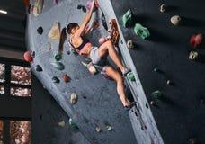 Fachowy żeński arywisty obwieszenie na bouldering ścianie, praktyka wspina się indoors zdjęcie stock