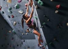 Fachowy żeński arywisty obwieszenie na bouldering ścianie, praktyka wspina się indoors fotografia royalty free