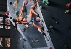 Fachowy żeński arywisty obwieszenie na bouldering ścianie, praktyka wspina się indoors obraz royalty free