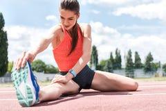 Fachowy żeński jogger robi rozgrzewce na śladzie obraz stock