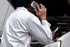 Fachowy automobilowy mechanik opowiada na telefonie i egzamininuje silnika pod kapiszonem samochód przy remontowym garażem w mund zdjęcia stock