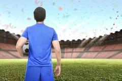 Fachowy azjatykci gracz piłki nożnej trzyma piłkę fotografia stock