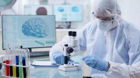 Fachowy badacz patrzeje pr?bk? krwi w ochronnym coverall zbiory wideo
