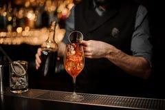 Fachowy barman nalewa wyśmienicie koktajl od stalowej osadzarki zdjęcie stock