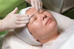 Fachowy beautician w zielonej sukni myje twarz zrelaksowana Muzułmańska kobieta z mydłem Wschodnia dziewczyna na procedurze dla zdjęcia stock