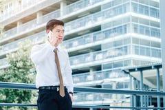 Fachowy biznesmen używa smartphone opowiada na jego telefonie s Zdjęcia Royalty Free