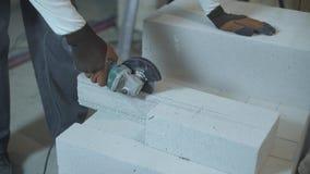 Fachowy budowniczy pracuje z elektrycznym ostrzarzem przy budową zbiory