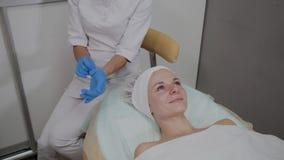 Fachowy cosmetologist jest ubranym błękitne gumowe rękawiczki dla procedury zbiory wideo