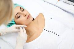 Fachowy cosmetologist robi zastrzykowi w twarzy, wargi Młoda kobieta obrysowywa dostaje strzykawkę z napełniaczem dla twarzy lub Obraz Royalty Free