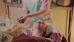 Fachowy cosmetologist usuwa maskę od twarzy starsza kobieta Cosmetological innowacje zbiory